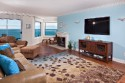 Solana Surfsong - spacious living room with large flat screen TV, fireplace and ocean views